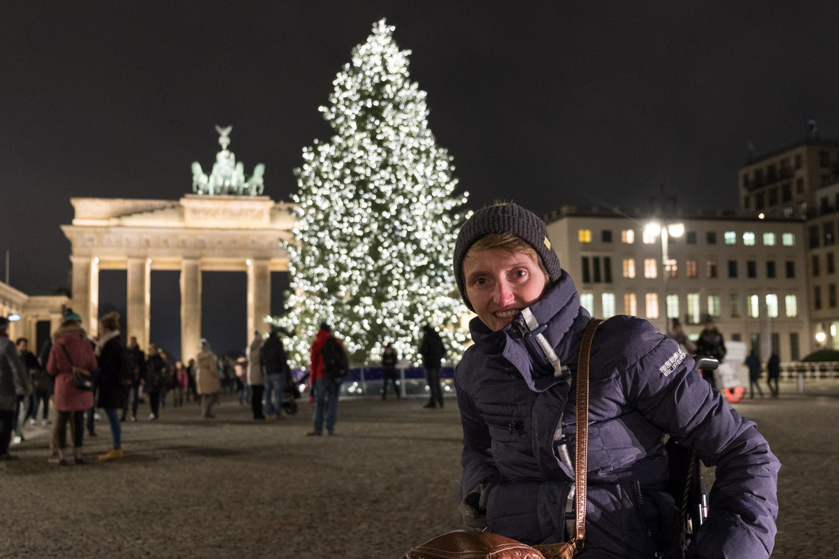 Tina in front of Brandenburg Gate in Berlin, with a lit christmas tree in the background