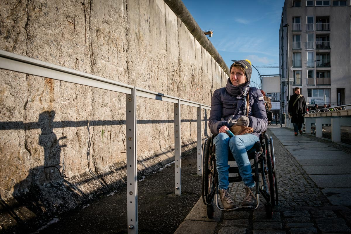 Tina Evans in Berlin. Tina is in her wheelchair looking at the Berlin Wall
